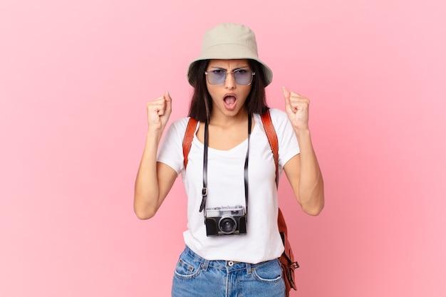Turista hispânica bonita gritando agressivamente com uma expressão de raiva com uma câmera fotográfica e um chapéu