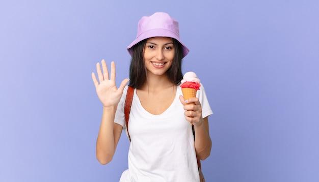 Turista hispânica bonita sorrindo e parecendo amigável, mostrando o número cinco e segurando um sorvete