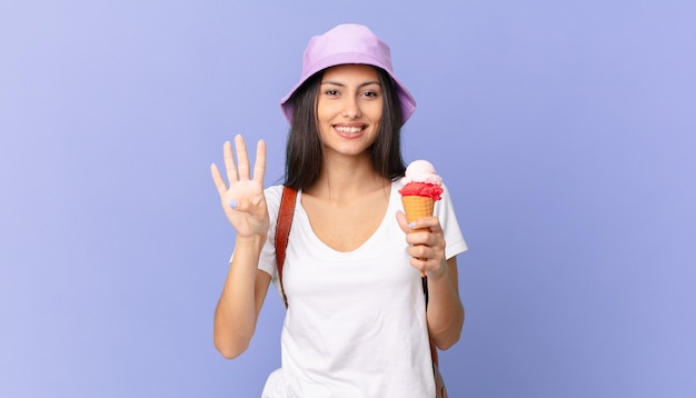 Turista hispânica bonita sorrindo e parecendo amigável, mostrando o número quatro e segurando um sorvete