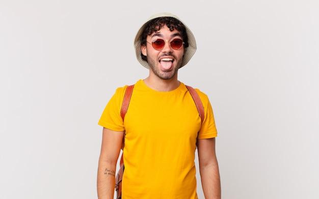 Turista hispânico com atitude alegre, despreocupada e rebelde, brincando e mostrando a língua, se divertindo