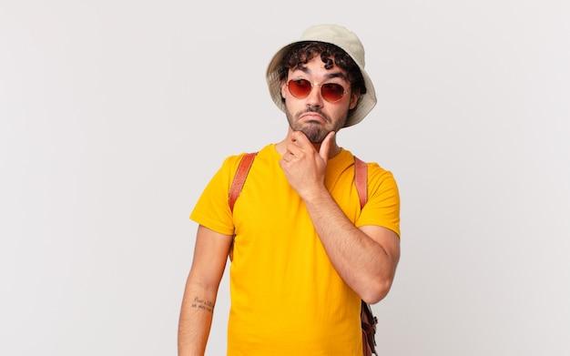 Turista hispânico pensando, se sentindo duvidoso e confuso, com diferentes opções, se perguntando qual decisão tomar