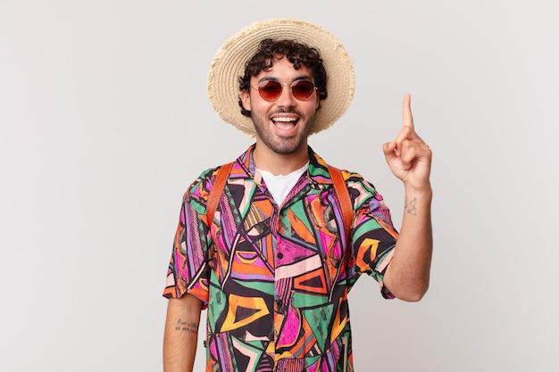 Turista hispânico se sentindo um gênio feliz e animado depois de realizar uma ideia, levantando o dedo alegremente, eureka!