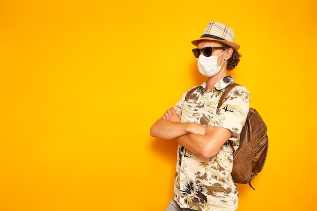 Turista homem com máscara médica cruzou os braços no peito olha para uma área vazia isolar fundo amarelo