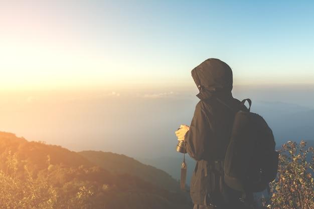 Turista homem de pé no pico da montanha com luz vintage