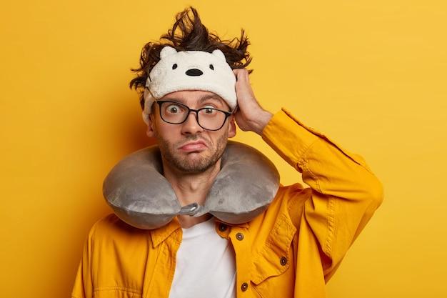 Turista intrigado coça a cabeça e considera seu erro, olha por trás dos óculos, usa uma almofada de pescoço para viajar no transporte