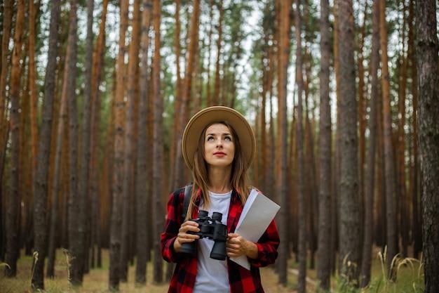 Turista jovem com um chapéu, camisa xadrez vermelha segura um mapa e binóculos na floresta.
