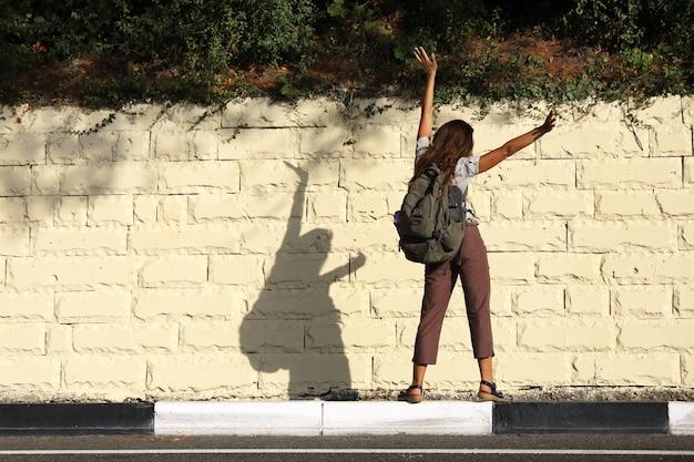 Turista jovem em pé de costas para a estrada na beira do meio-fio e agitando os braços