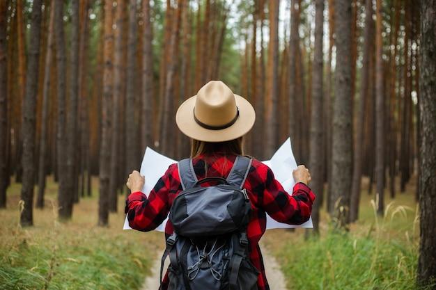 Turista jovem em um chapéu, camisa xadrez vermelha segura um mapa da área da floresta.