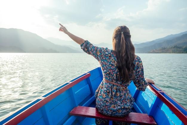 Turista jovem em um lindo vestido está nadando no lago de barco e aprecia a paisagem das montanhas. o conceito de atividades ao ar livre. vista traseira