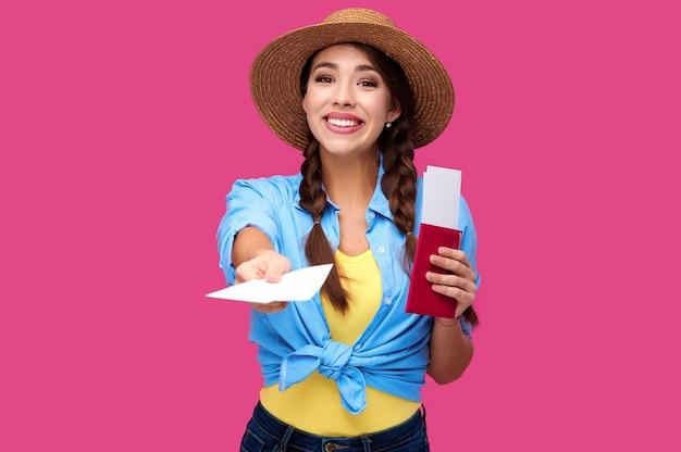Turista jovem sorridente com passaporte dando passagem aérea. viajante caucasiano com roupas casuais de verão em fundo rosa isolado. aluna com documento