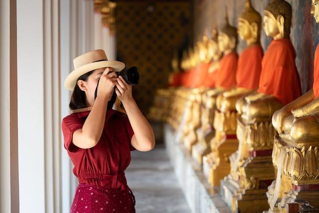 Turista linda mulher held câmera para capturar as memórias. templo wat arun