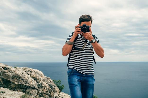 Turista masculino fotógrafo com uma câmera digital profissional e lente