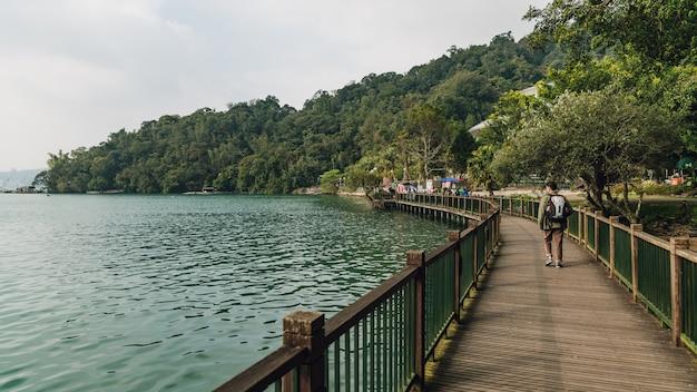 Turista masculino que anda na passagem de madeira ao longo do lado com o lago e as árvores sun moon.