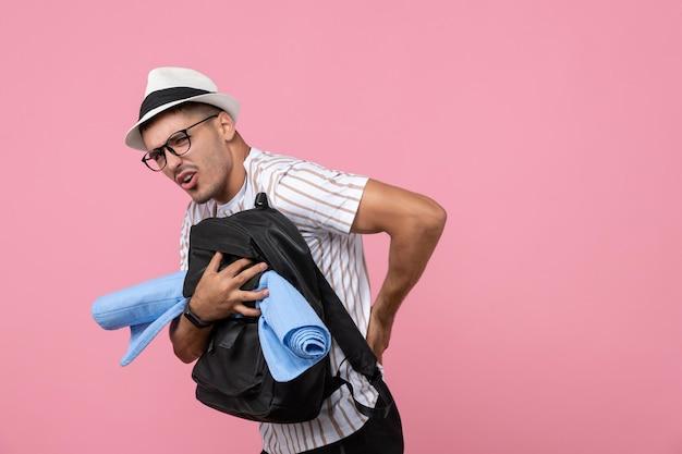 Turista masculino segurando sua mochila na parede cor de rosa turista
