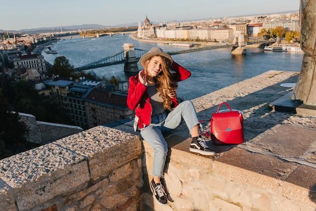 Turista muito feminina em roupa vermelha, curtindo os passeios turísticos em um país europeu e rindo