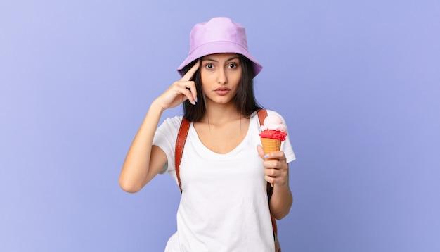 Turista muito hispânica parecendo surpresa, percebendo um novo pensamento, ideia ou conceito e segurando um sorvete