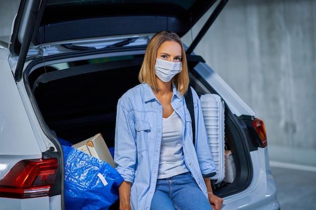 Turista mulher adulta usando máscara devido a procedimentos covid-19 no estacionamento subterrâneo do aeroporto