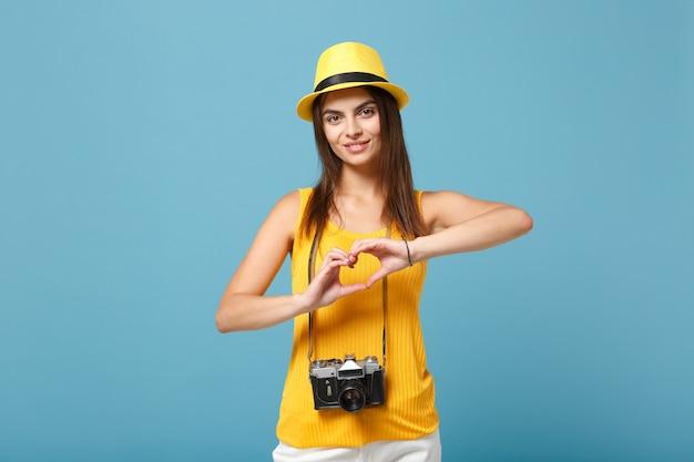 Turista mulher com roupas casuais de verão amarelo e chapéu com câmera fotográfica azul