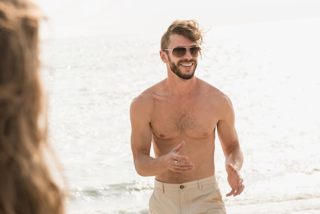 Turista muscular sem camisa, andando na praia no verão