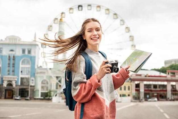 Turista na cidade e roda gigante atrás