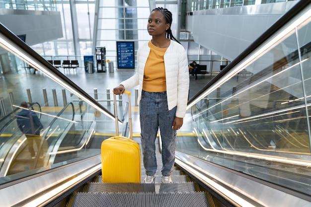 Turista negra com mala na escada rolante em viagens de aeroporto ou estação ferroviária