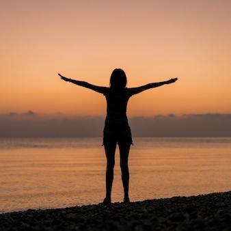 Turista no nascer do sol, segurando as mãos no ar