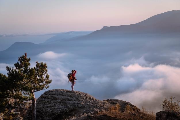Turista no topo do penhasco fotografa as montanhas em um dia de neblina, turismo de concentração, recreação ativa, beleza da natureza