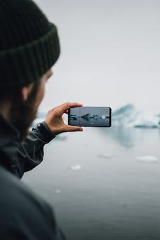 Turista observa geleira na água na islândia