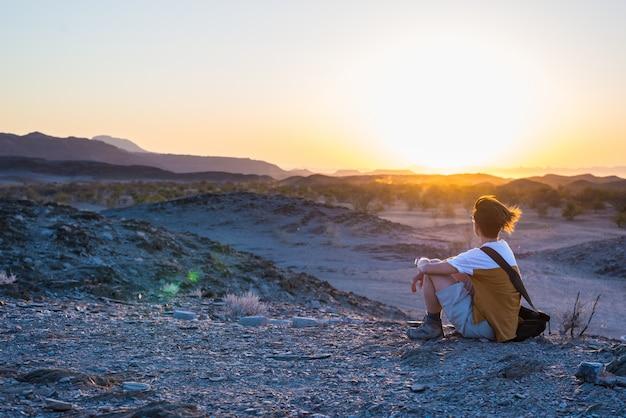 Turista, observando a vista deslumbrante do vale estéril e montanhas