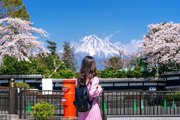 Turista olhando para a montanha fuji e a flor de cerejeira na primavera, fujinomiya no japão.