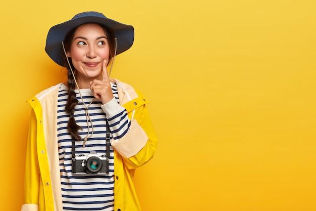 Turista pensativa mantém o dedo indicador na bochecha, pensa em como escolher, explora os arredores durante a caminhada, usa câmera retro no pescoço, capacete e capa de chuva amarela impermeável
