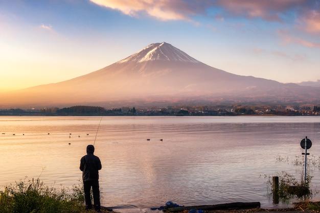 Turista pescando com a montanha fuji no lago kawaguchiko ao amanhecer