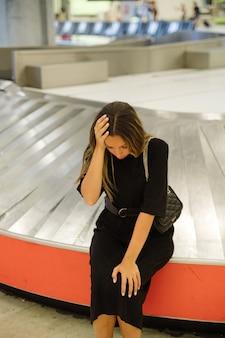 Turista preocupada sentada perto da esteira rolante no aeroporto por causa da mala perdida