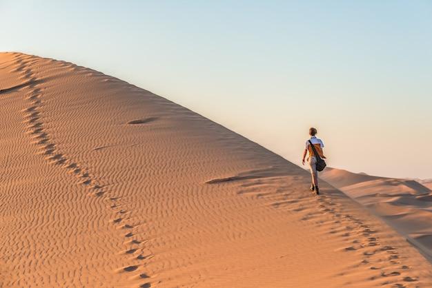 Turista que anda nas dunas de areia em sossusvlei, deserto de namib, parque nacional de namib naukluft, namíbia.