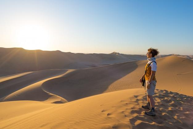 Turista que está em dunas de areia e que olha a vista em sossusvlei, deserto de namib, destino do curso em namíbia, áfrica.