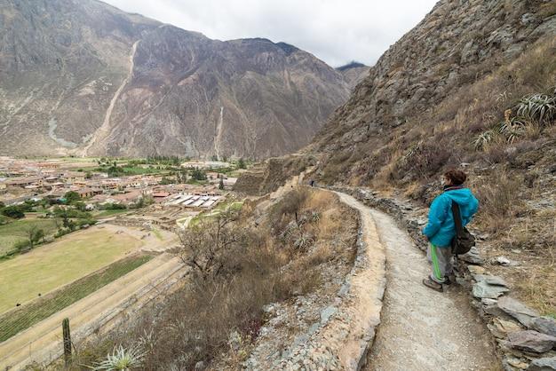 Turista que explora o inca trails e o sítio arqueológico em ollantaytambo, vale sagrado, destino do curso na região de cusco, peru. férias e aventuras na américa do sul.