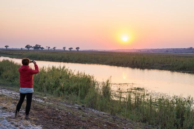 Turista que toma a foto com o smartphone no por do sol majestoso sobre chobe river, beira de namíbia botswana, áfrica. cores naturais, vista traseira.