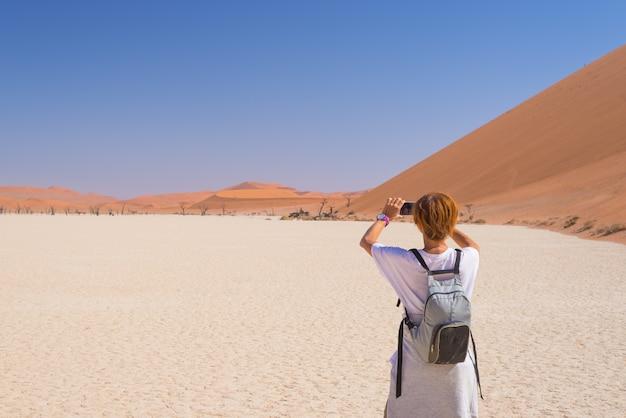Turista que toma a foto com o telefone esperto em sossusvlei, deserto de namib, parque nacional de namib naukluft.