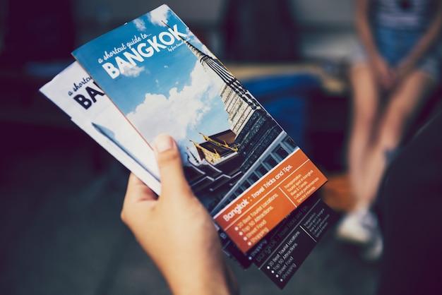 Turista segurando brochuras de guia de viagens de banguecoque
