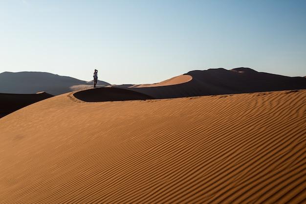 Turista, segurando o telefone inteligente e tirando foto em dunas de areia cênica em sossusvlei