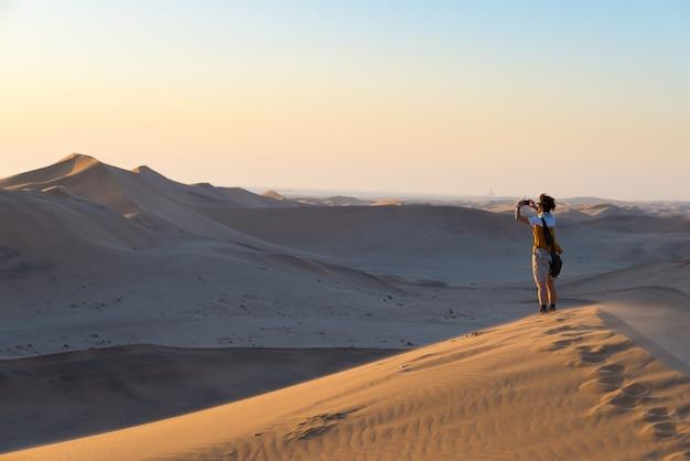 Turista, segurando o telefone inteligente e tirando foto em dunas de areia cênica iluminada