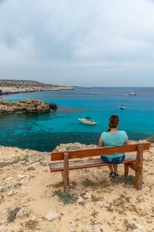 Turista senta-se em um banco de madeira perto da lagoa azul