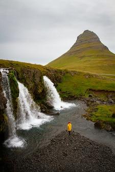 Turista sob a cachoeira na islândia aventura foto editar sp