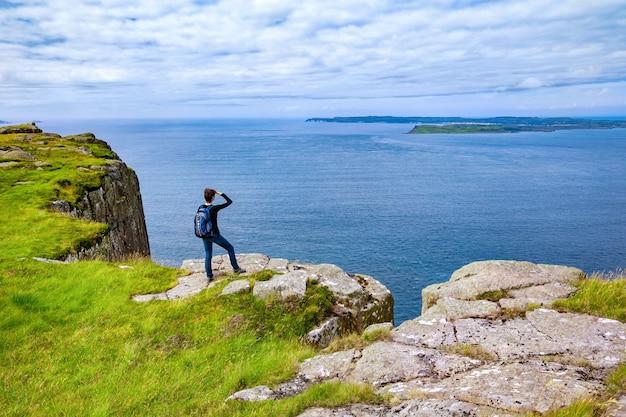 Turista solitária com uma mochila na falésia fair head