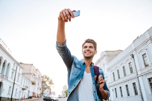 Turista sorridente com mochila fazendo selfies isoladas em belos edifícios modernos localizados no centro da cidade
