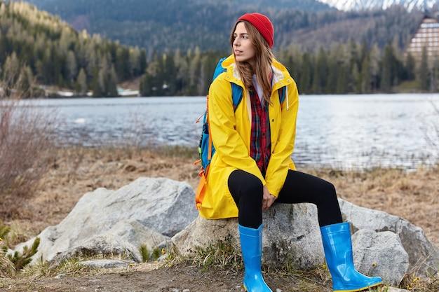 Turista sorridente e pensativa usando capa de chuva amarela e botas de borracha sentada na pedra