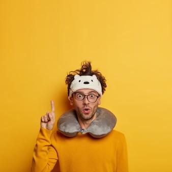 Turista surpreso posa na sala de espera, usa travesseiro no pescoço e tem uma expressão facial chocada