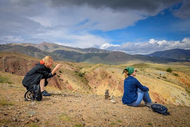 Turista tira fotos de sua amiga no smartphone em um belo ponto de vista.
