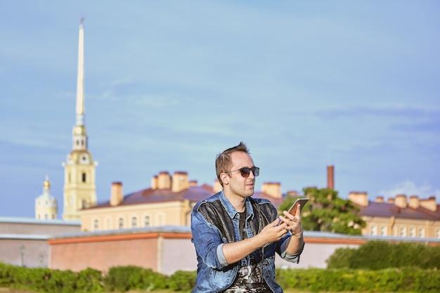 Turista tira fotos dos pontos turísticos de são petersburgo, na rússia, usando telefone celular.