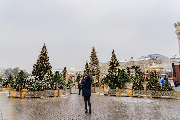 Turista tira uma foto da praça decorada de natal